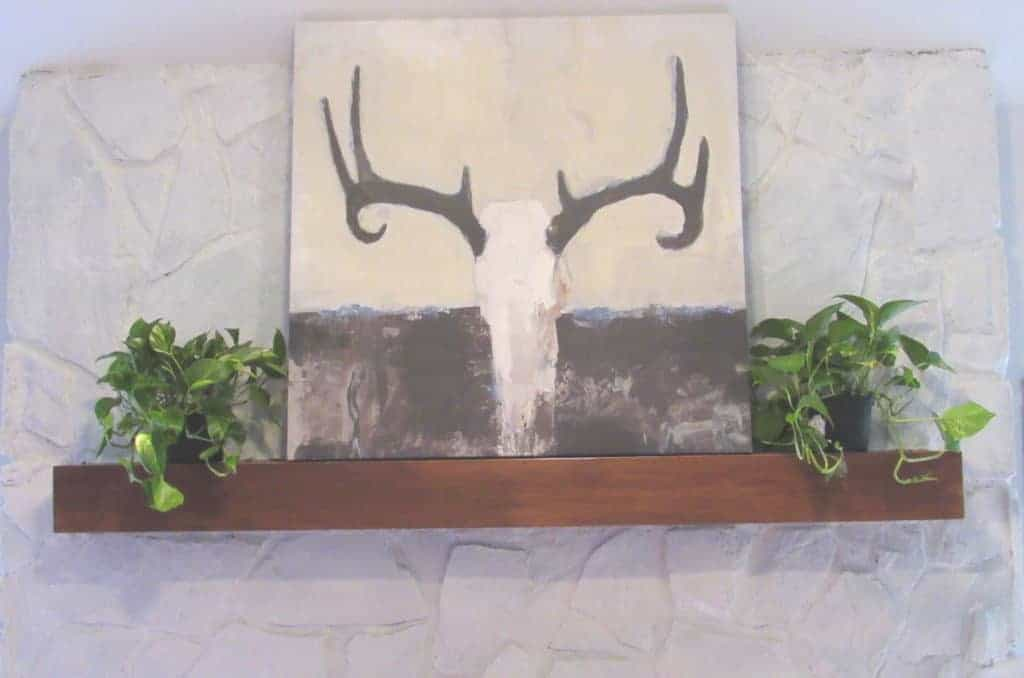 decorate a fireplace mantel with art work