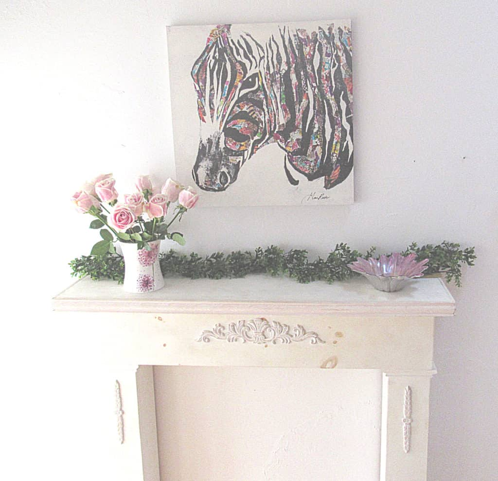 decorate a fireplace mantel with artwork and flowers