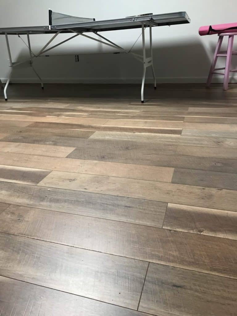 Finished basement room with laminate flooring on concrete