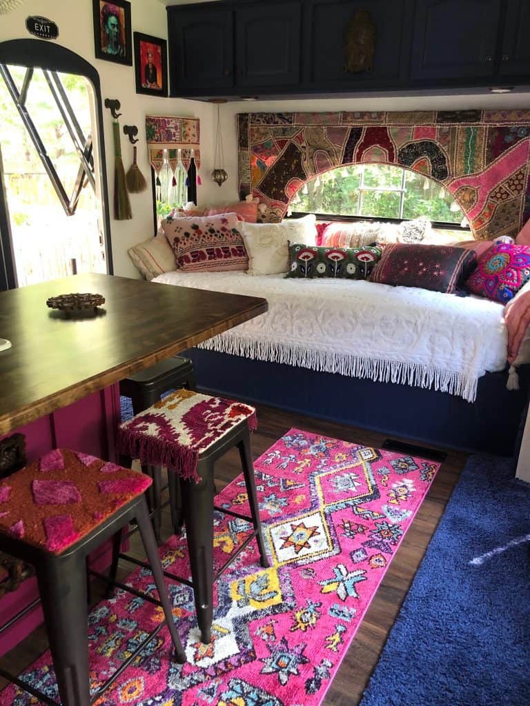 How to remodel an RV pretty colorful (Boho Style), Daybed covered with colorful pillows and a bright white throw.