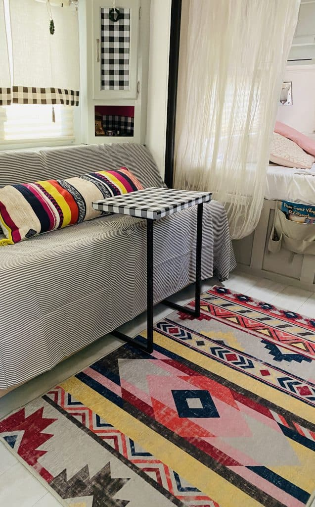 camper remodel, adding a colorful rug, colorful pillows and a pretty throw on top of the Jack Knife Sofa helps.