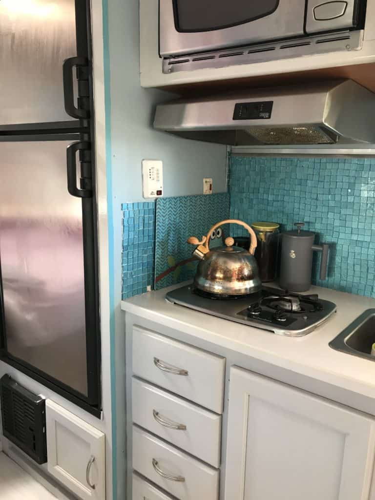 Camper kitchen cabinets painted and backsplash in a light teal color.