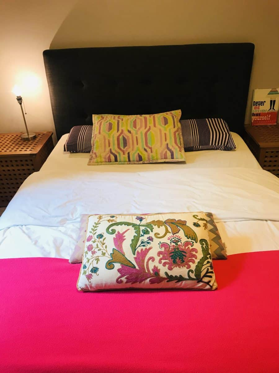bed with a pink throw and pillows