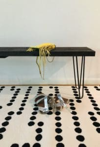 bench in entrance with yello purse