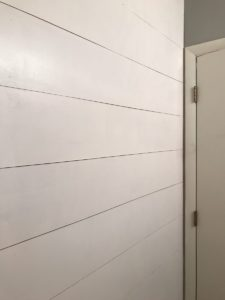 Painted shiplap wall covers all the holes in the wall. Very cool and easy DIY project.